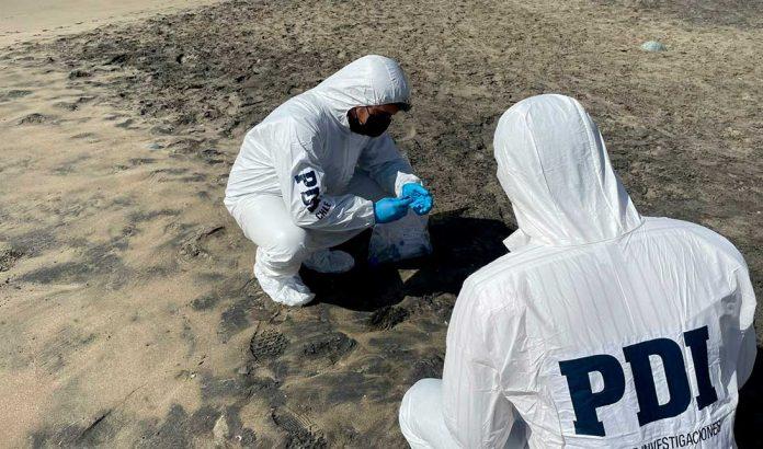 ARCHIVO | PDI examinando residuos en Playa Amarilla de Antofagasta